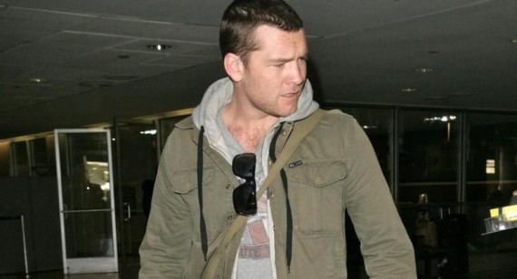 Sam Worthington is glad his girlfriend does not work