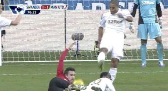 Ashley Williams kicks ball at Robin van Persie